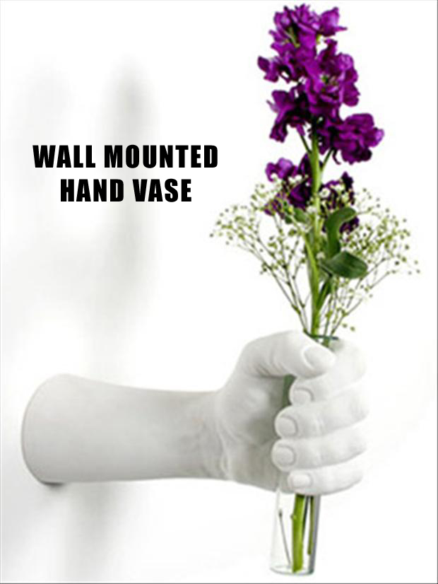 A creative vase that is wall mounted and is hand shaped