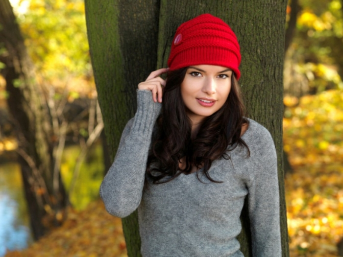 Smiling-brunette-wearing-red-beanie-hat-fall-scene-700x525