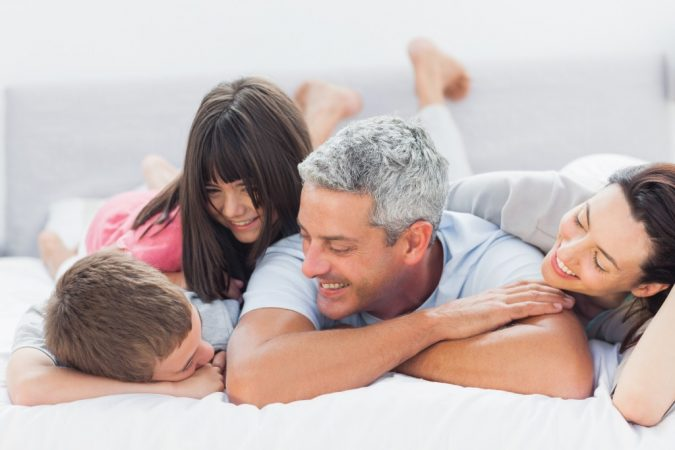 Cute family lying on bed and talking together at home
