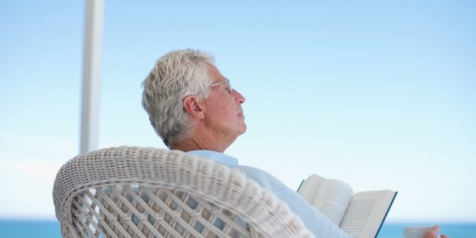 Senior man reading book on beach patio