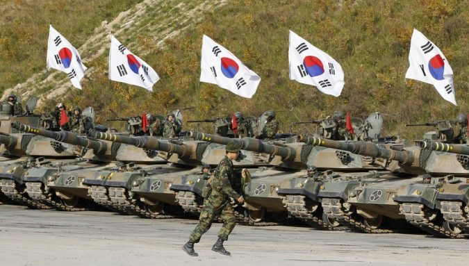 A South Korean army soldier runs in front of K-1 tanks after a live-fire military exercise as a part of the Seoul International Aerospace and Defense Exhibition 2011 on the Seungjin fire training field in Pocheon, about 46 km (28 miles) northeast of Seoul and about 15 km (9 miles) south of the demilitarized zone separating the two Koreas October 20, 2011. REUTERS/Jo Yong-Hak (SOUTH KOREA - Tags: POLITICS MILITARY)