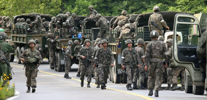 South Korean army soldiers exit their military trucks during an arrest operation in Goseong, South Korea, Monday, June 23, 2014. The parents of a runaway South Korean soldier suspected of killing five comrades at an outpost near the tense border with North Korea pleaded with him to surrender Monday as the military were besieging him and trying to capture him alive, officials said.(AP Photo/Yonhap, Hwang Kwang-mo) KOREA OUT