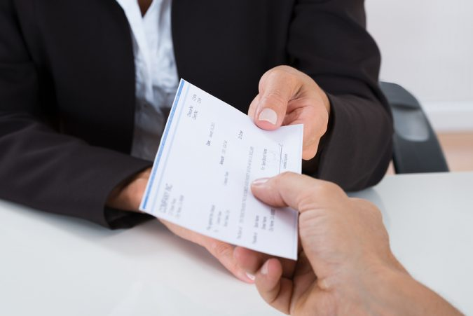 Close-up Of Businessperson Hands Giving Cheque To Other Person At Desk ** Note: Shallow depth of field
